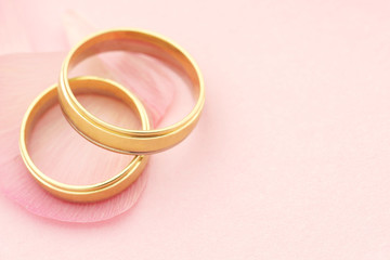 Wedding rings with flower petals on pink background