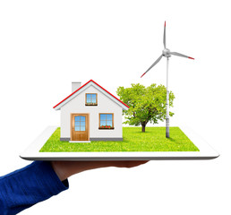 hand holding a tablet with a wind turbine and house