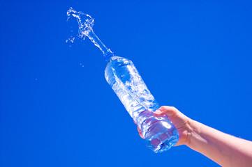 Pure water splashing from bottle against blue sky