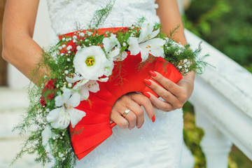 Bride holding beautiful red wedding flowers bouquet