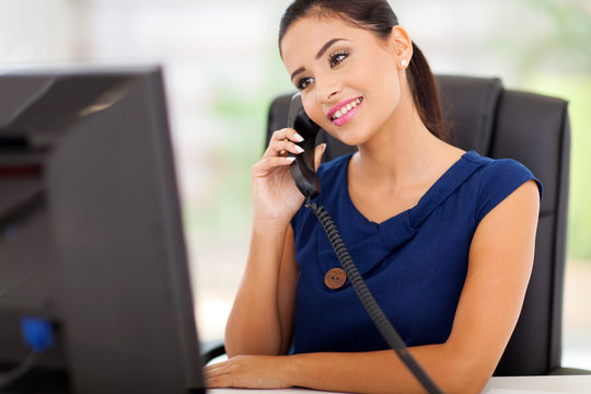 businesswoman answering telephone in her office