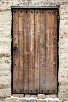 Ancient wooden door in old stone castle wall. Tallinn, Estonia
