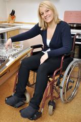 Junge Frau im Rollstuhl räumt Spülmaschine aus
