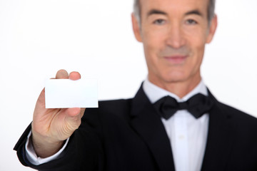 Silver service waiter holding up a business card