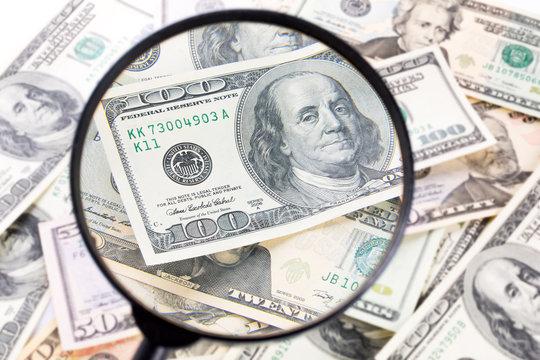 Hundred dollar banknote under magnifying glass