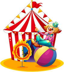 A clown sitting  above a ball beside a ring of fire in front of
