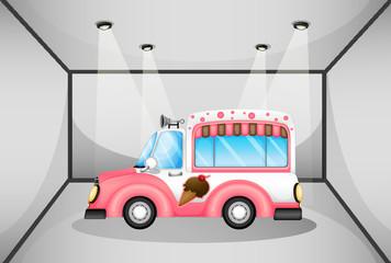 A pink ice cream car inside the garage