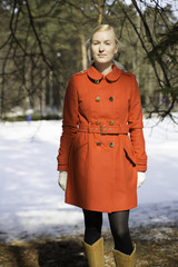 Young woman in red coat under spruce