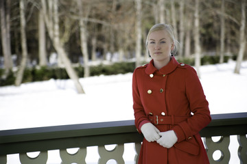 Young woman in red coat at terrace