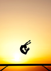 Wall Mural - female gymnast jumps on balance beam in sunset