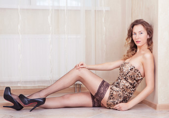 Cute woman lying on the floor stockings and leopard dress