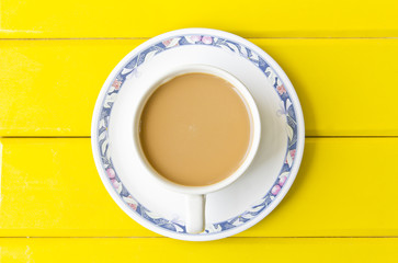 Cup of coffee over the yellow background