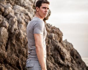 Portrait of adult handsome man against rock background.