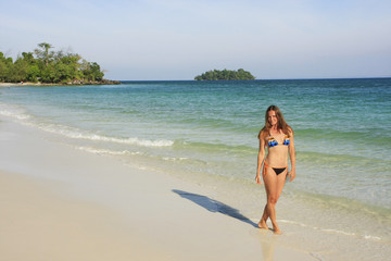 Young woman walking on a beach of Koh Rong island, Cambodia