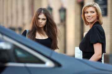 Two young women on the car parking