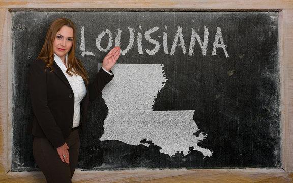 Teacher showing map of louisiana on blackboard