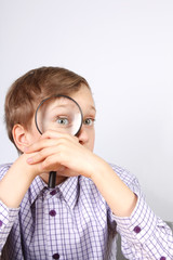 Young boy in purple shirt looking through a magnifying glass gri