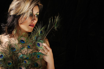 Woman in peacock feathers / female nude on a dark background cov