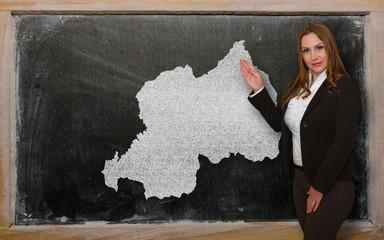 Teacher showing map of rwanda on blackboard