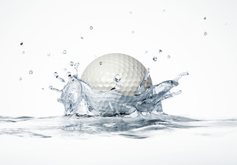 White golf ball splashing into water, forming a crown splash.
