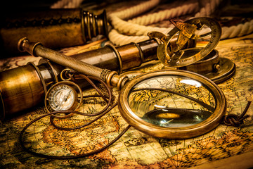 Wall Mural - Vintage magnifying glass lies on an ancient world map