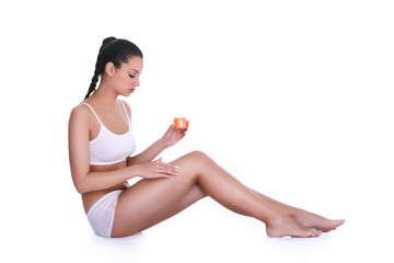 Young woman applying lotion on her body