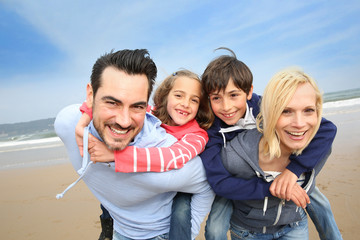 Wall Mural - Portrait of cheerful family at the beach