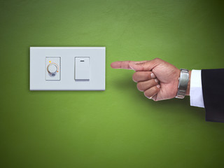 hand pointing to switch ofelectric appliance on green wall