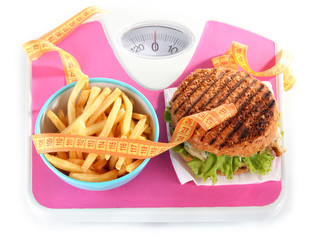 Hot-dog, hamburger and fries on scales isolated on white