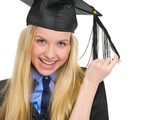 Portrait of happy young woman in graduation gown