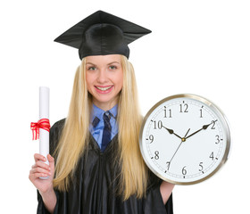 Happy young woman in graduation gown holding diploma and clock