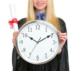 Closeup on diploma and clock in hand of woman in graduation gown