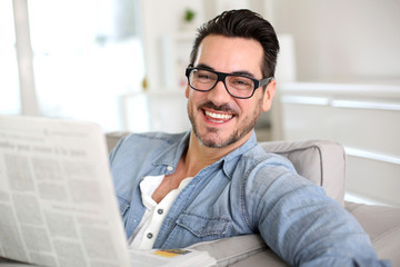 Cheerful guy reading newspaper in sofa
