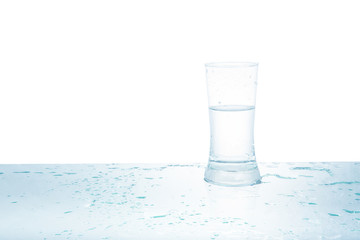 Glass of water with drops on white background