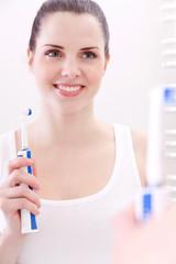 Junge hübsche brünette Frau mit einer Zahnbürste vor einem Sp
