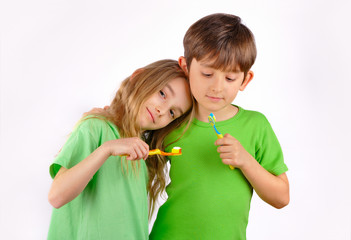 Health - boy and girl brush their teeth with toothbrushes