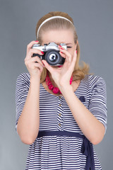 pinup woman in retro clothes posing with photo camera