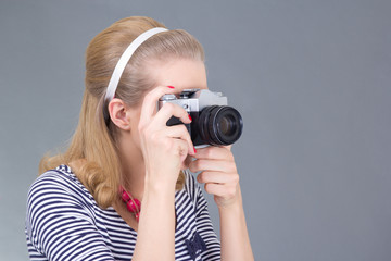 young woman in retro clothes posing with photo camera