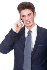 Angry young executive using cellphone, closeup portrait on white
