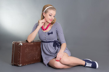 beautiful pinup girl sitting with brown retro suitcase
