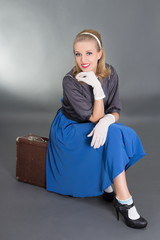 young beautiful pinup girl sitting on retro suitcase over grey