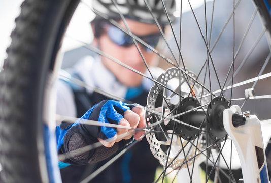Young Man Repairing Bicycle Wheel
