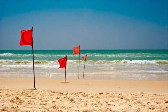 Swimming is dangerous in ocean waves. Red warning flag flapping