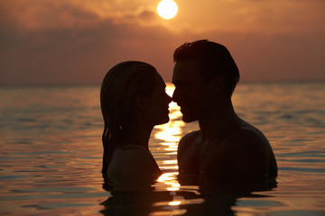 Silhouette Of Romantic Couple Standing In Sea