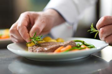 Chef hands decorating a dish in restaurant kitchen