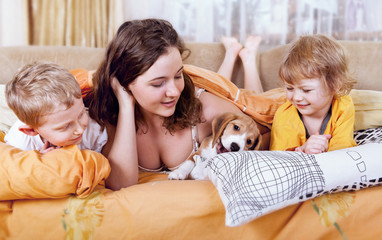 Children playing with puppy in bed