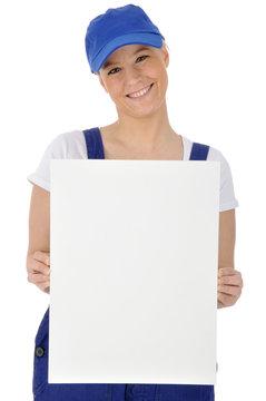 Freundliche junge Handwerkerin hält leeres Schild