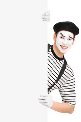Smiling mime artist posing behind a blank panel
