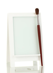 Photo frame as easel with brush isolated on white