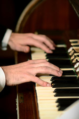 Male hands playing on piano